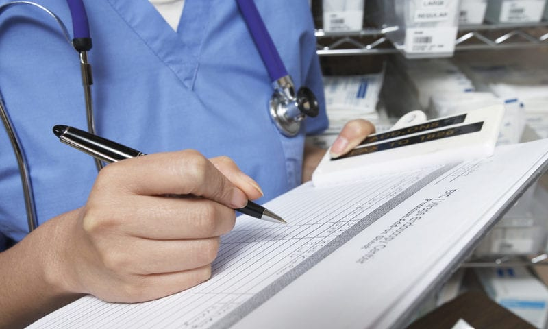 Female doctor writing in patient chart,
